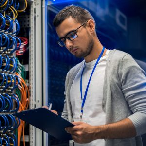 network engineer checking a server cabinet, at supercomputer in data center
